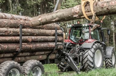 Valtra tractor with Kesla trailer in the forest loading timber.